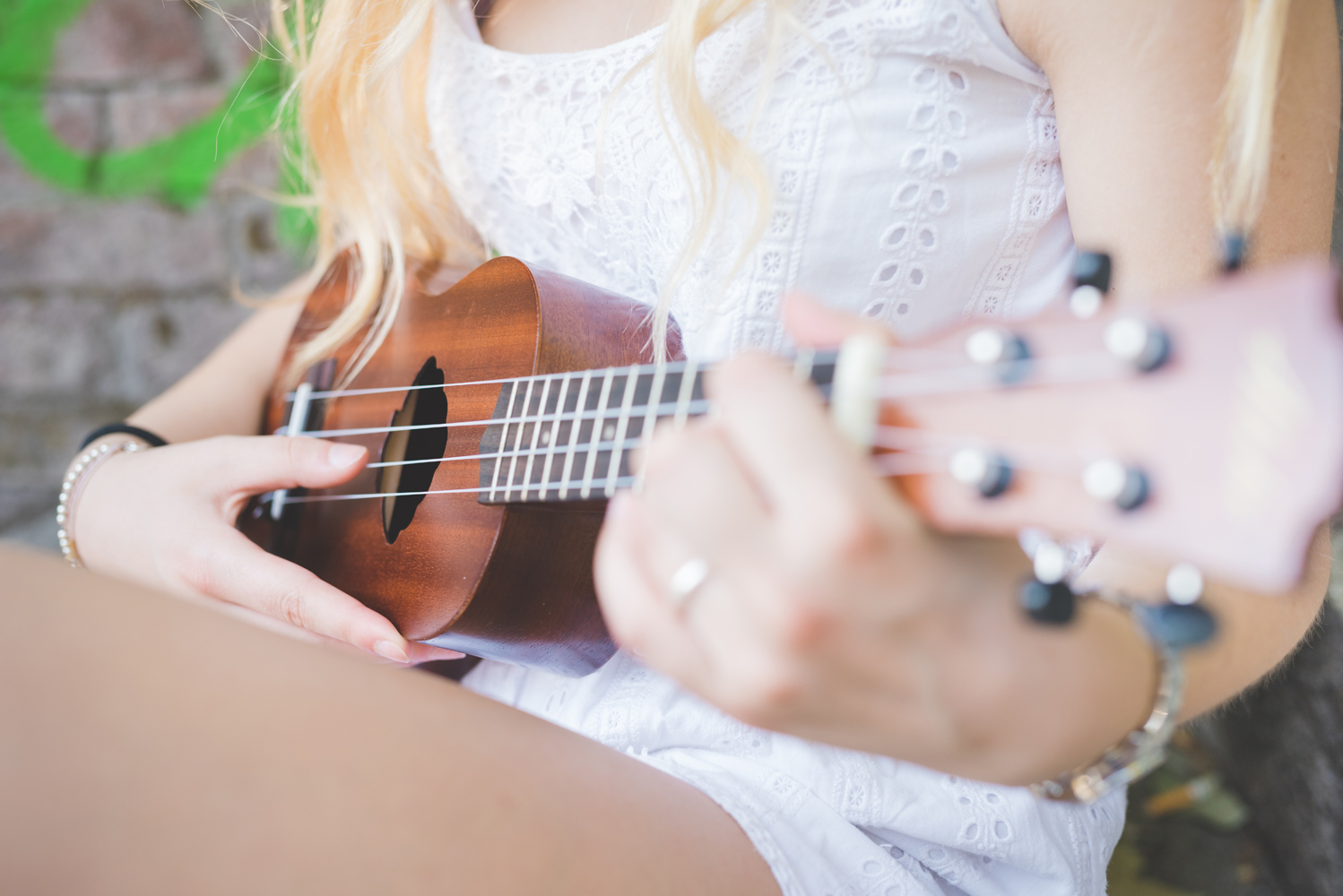 graphicstock close up hand young millennial caucasian woman playing ukulele music song chord concept STQ pF1W